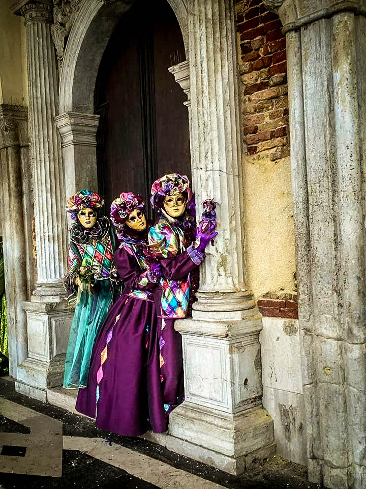 People posing with colorful masks and clothing in Venice