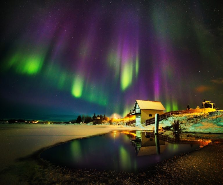 The less light pollution you have, the clearer the aurora. It's true that buildings and houses create better compositions, but that is a risk you have to take