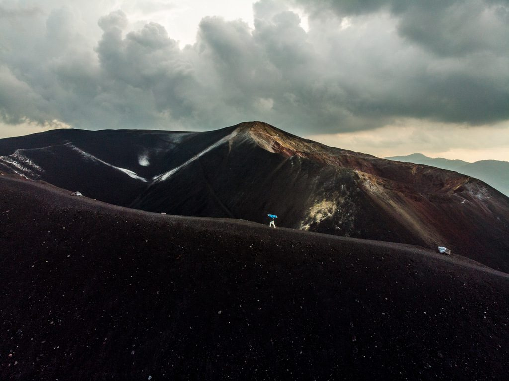 Climbing up Cerro Negro with a sandboard in hand