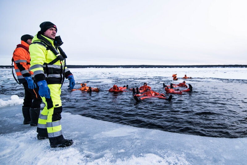 Travelers taking a swim with a dry suit in Swedish Lapland