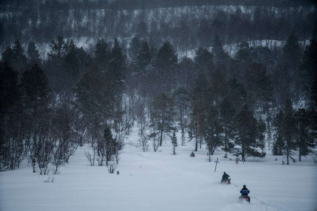 Travelers use snowmobiles to get deeper into the Swedish forest