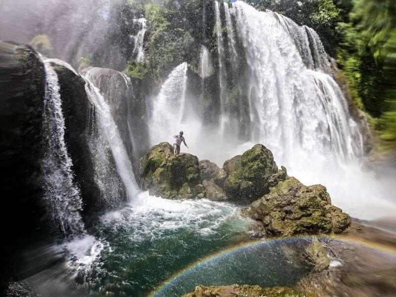 Jumping in the water at Standing below the Pulhapanzak Waterfalls