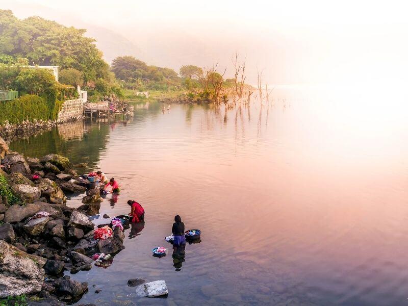 Women at sunrise washing clothes at Lake Atitlan